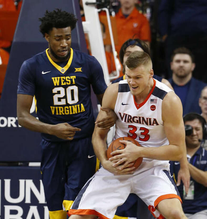 Virginia center Jack Salt (33) and West Virginia forward Brandon Watkins (20) fight for a rebound during the first half of an NCAA college basketball game in Charlottesville, Va., Saturday, Dec. 3, 2016. (AP Photo/Steve Helber)