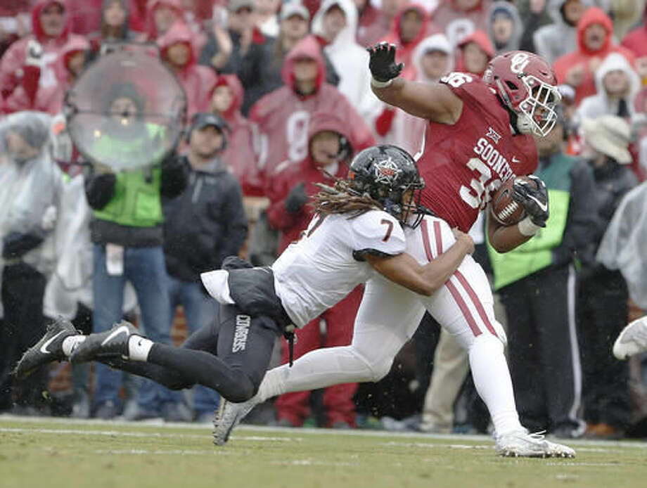 Oklahoma fullback Dimitri Flowers (36) is tackled by Oklahoma State cornerback Ramon Richards (7) during the first half of an NCAA college football game, Saturday, Dec. 3, 2016, in Norman, Okla. (AP Photo/Alonzo Adams)