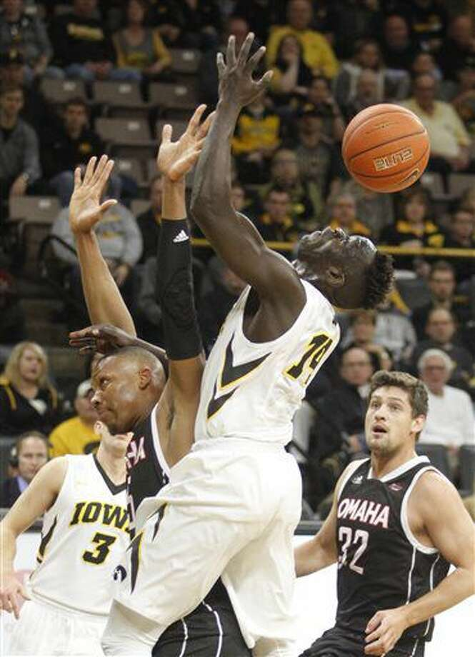 Iowa's Peter Jok (14) is fouled by Omaha's Tre'Shawn Thurman (15) during the first half of an NCAA college basketball game, Saturday, Dec. 3, 2016, in Iowa City, Iowa. (AP Photo/Matthew Holst)