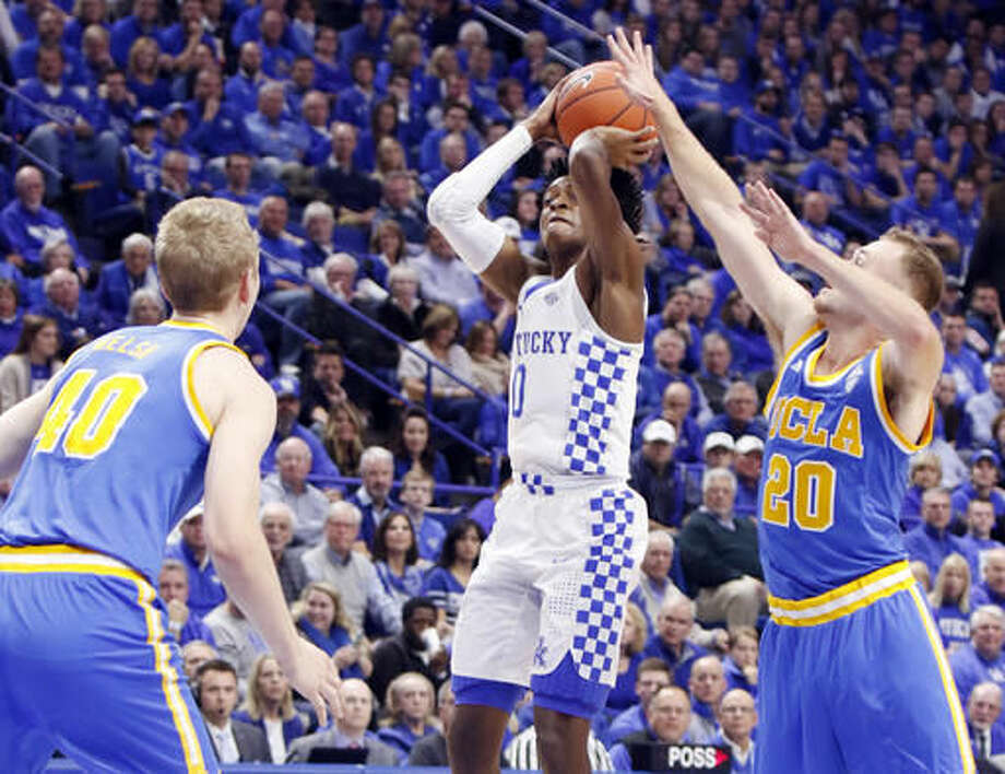 Kentucky's De'Aaron Fox, middle, shoots near the defense of UCLA's Bryce Alford (20) and Thomas Welsh (40) during the first half of an NCAA college basketball game, Saturday, Dec. 3, 2016, in Lexington, Ky. (AP Photo/James Crisp)