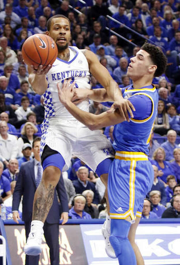 Kentucky's Isaiah Briscoe, left, passes near UCLA's Lonzo Ball during the first half of an NCAA college basketball game, Saturday, Dec. 3, 2016, in Lexington, Ky. (AP Photo/James Crisp)