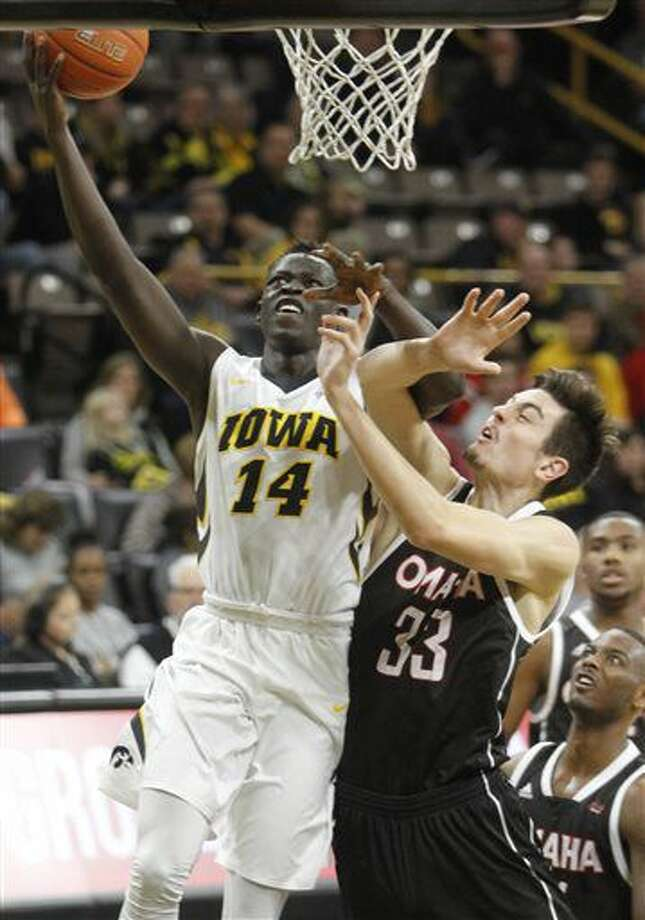 Iowa's Peter Jok (14) goes to the basket against Omaha's Zach Pirog (33) during the first half of an NCAA college basketball game, Saturday, Dec. 3, 2016, in Iowa City, Iowa. (AP Photo/Matthew Holst)