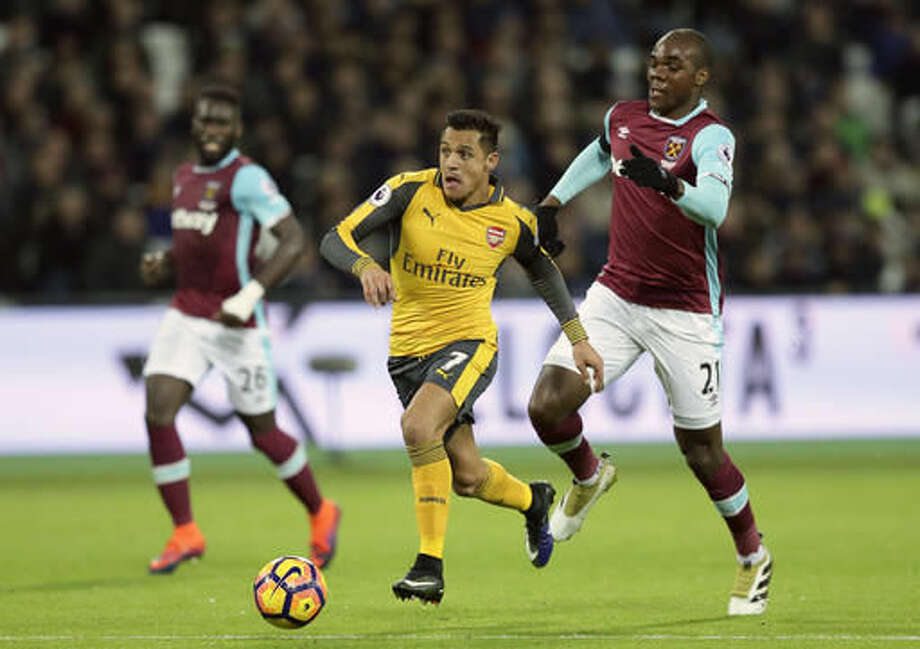 Arsenal's Alexis Sanchez, center, breaks past West Ham's Angelo Ogbonna Obinze during the English Premier League soccer match between West Ham United and Arsenal at The London Stadium in London, Saturday Dec. 3, 2016. (AP Photo/Tim Ireland)