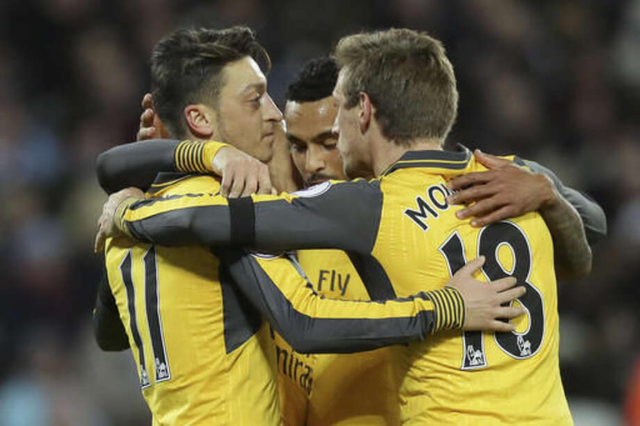 Arsenal's Mesut Ozil, left, celebrates after scoring a goal, with team mates Theo Walcott, centre, and Nacho Monreal during the English Premier League soccer match between West Ham United and Arsenal at The London Stadium in London, Saturday Dec. 3, 2016. (AP Photo/Tim Ireland)