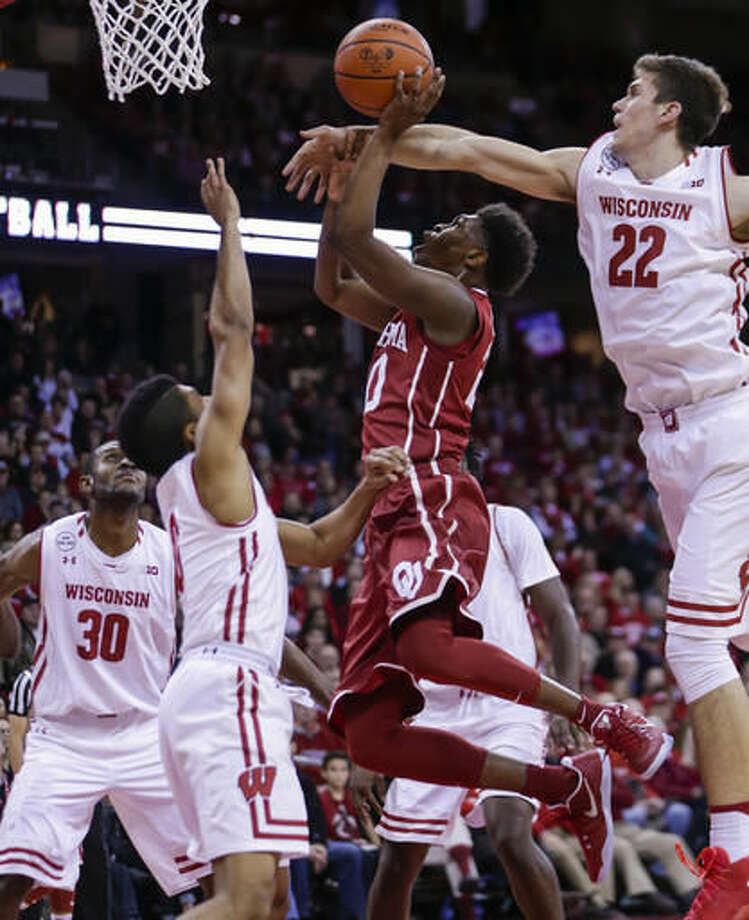 Wisconsin's Ethan Happ (22) fouls Oklahoma's Kameron McGusty, center, during the first half of an NCAA college basketball game Saturday, Dec. 3, 2016, in Madison, Wis. At left is Wisconsin's D'Mitrik Trice (0). (AP Photo/Andy Manis)