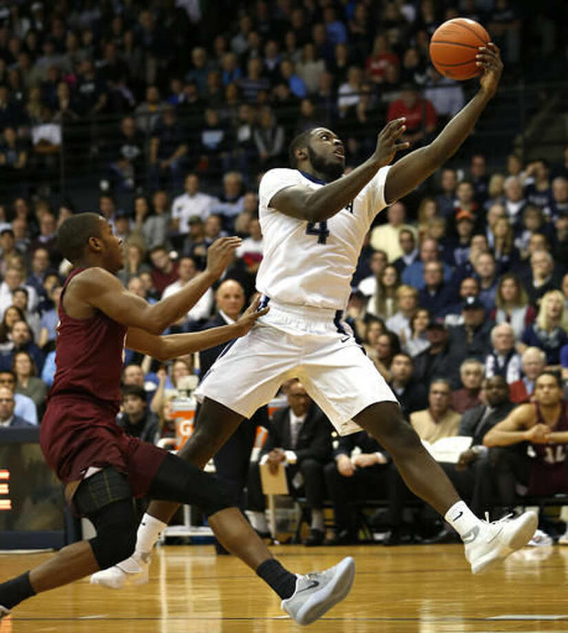 Villanova forward Eric Paschall (4) reaches for a pass as Saint Joseph's forward Markell Lodge (23) chases in the first half of an NCAA college basketball game, Saturday, Dec. 3, 2016, in Villanova, Pa. (AP Photo/Laurence Kesterson)