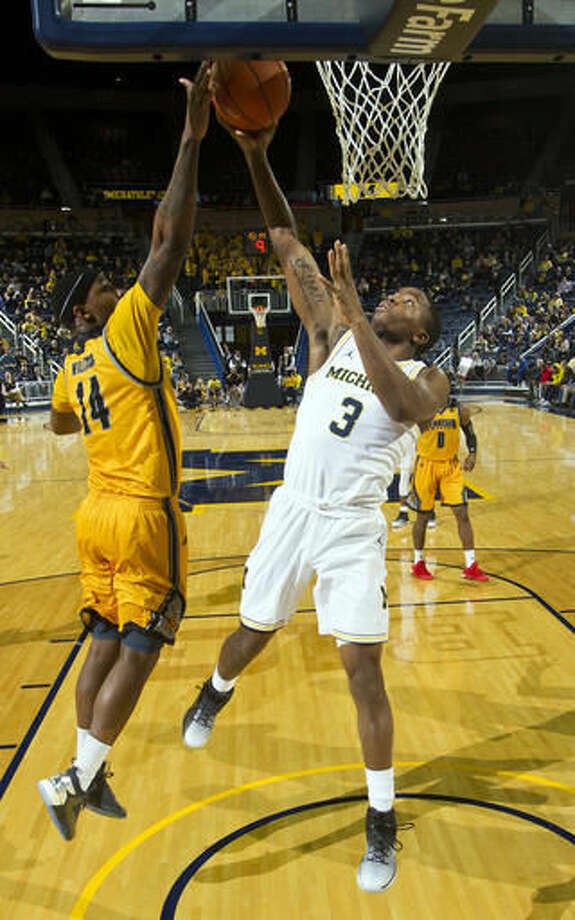 Kennesaw State forward Aubrey Williams (14) defends against Michigan guard Xavier Simpson (3) in the second half of an NCAA college basketball game at Crisler Center in Ann Arbor, Mich., Saturday, Dec. 3, 2016. (AP Photo/Tony Ding)