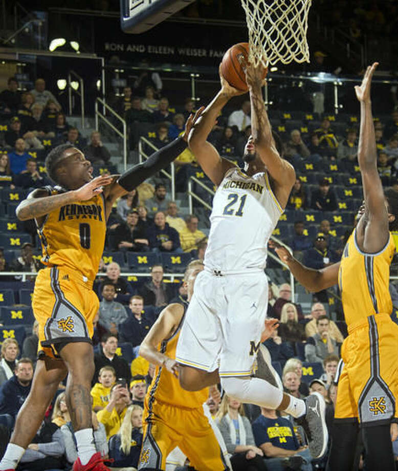 Kennesaw State guard Kendrick Ray (0) defends as Michigan guard Zak Irvin (21) goes to the basket in the first half of an NCAA college basketball game at Crisler Center in Ann Arbor, Mich., Saturday, Dec. 3, 2016. (AP Photo/Tony Ding)