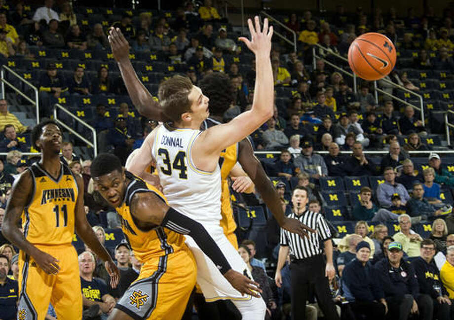 Kennesaw State guard Kendrick Ray, bottom, collides with Michigan forward Mark Donnal (34) in the first half of an NCAA college basketball game at Crisler Center in Ann Arbor, Mich., Saturday, Dec. 3, 2016. (AP Photo/Tony Ding)