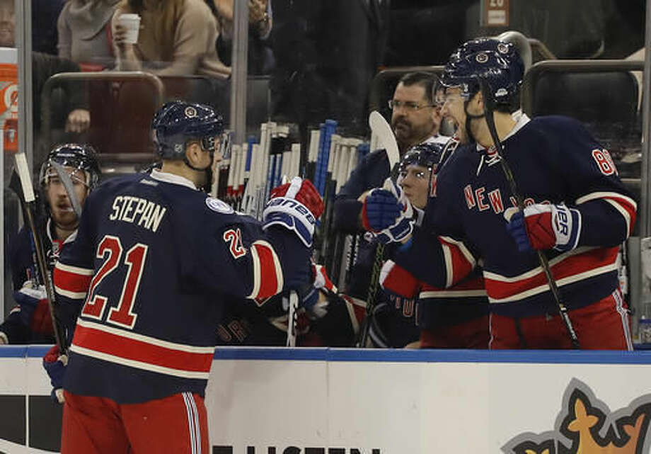 New York Rangers center Derek Stepan (21) is congratulated by teammates after scoring a goal against the Carolina Hurricanes during the first period of an NHL hockey game, Saturday, Dec. 3, 2016, in New York. (AP Photo/Julie Jacobson)