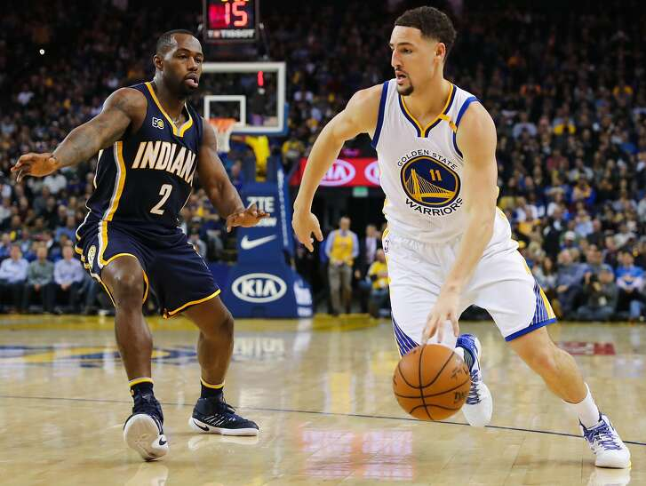 Golden State Warriors' Klay Thompson, #11 (right) drives the ball against the Indiana Pacers during the first half of an NBA basketball game, in Oakland, California, on Monday, Dec. 5, 2016.