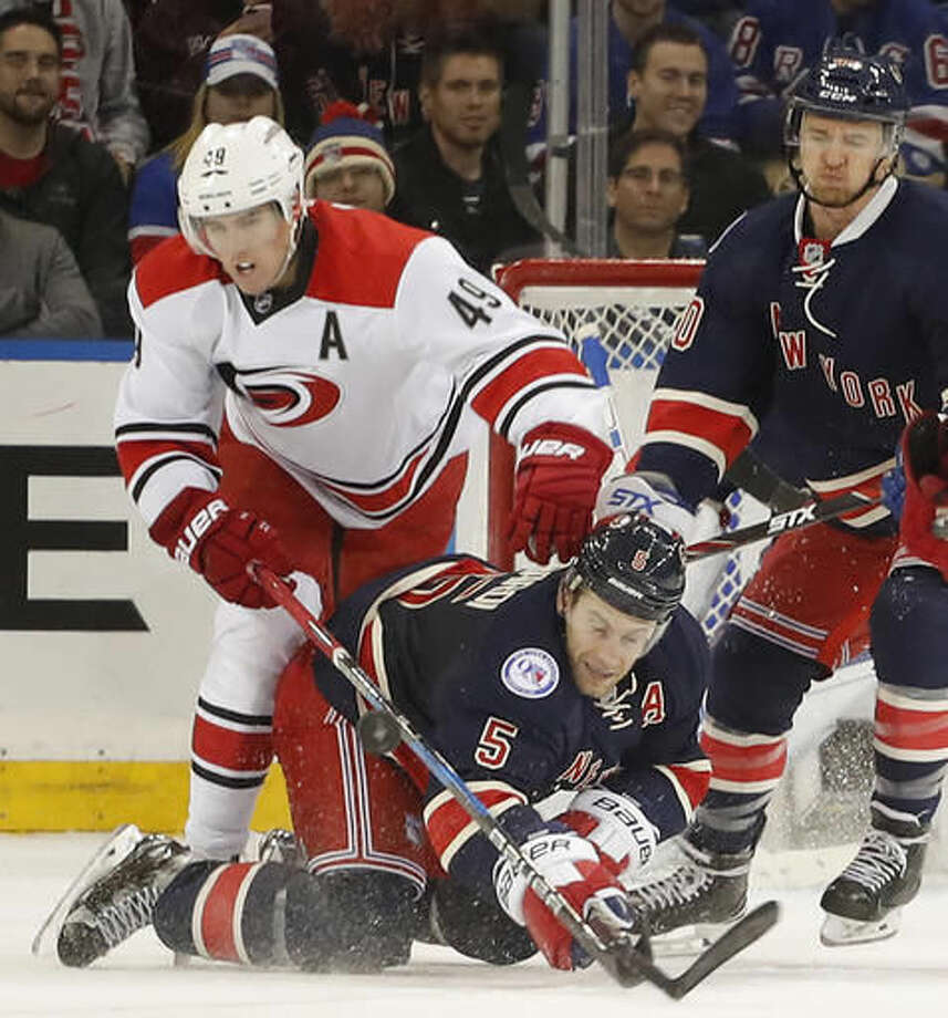 New York Rangers defenseman Dan Girardi (5) hits the ice as he vies for control of the puck against Carolina Hurricanes center Victor Rask (49) during the second period of an NHL hockey game, Saturday, Dec. 3, 2016, in New York. (AP Photo/Julie Jacobson)