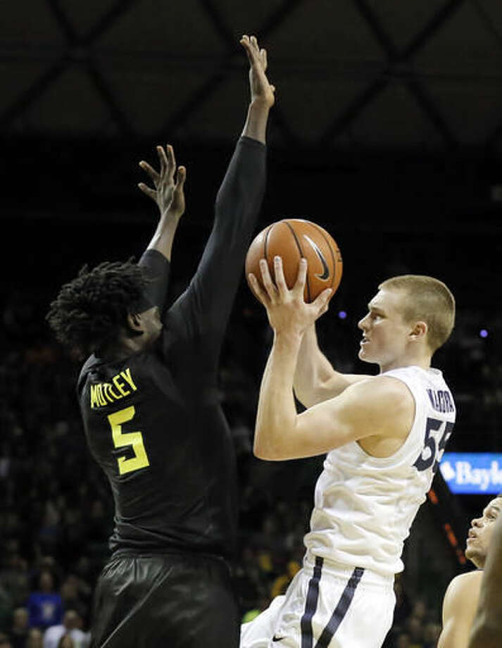 Baylor forward Johnathan Motley (5) defends as Xavier's J.P. Macura (55) leaps to the basket for a shot-attempt in the first half of an NCAA college basketball game, Saturday, Dec. 3, 2016, in Waco, Texas. (AP Photo/Tony Gutierrez)