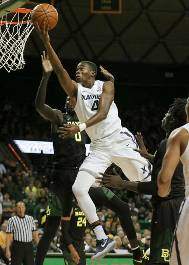 Xavier guard Edmond Sumner (4) cuts through Baylor defenders Jo Lual-Acuil Jr. of Australia, rear, and Johnathan Motley, right, as he attempts to shoot in the first half of an NCAA college basketball game, Saturday, Dec. 3, 2016, in Waco, Texas. (AP Photo/Tony Gutierrez)