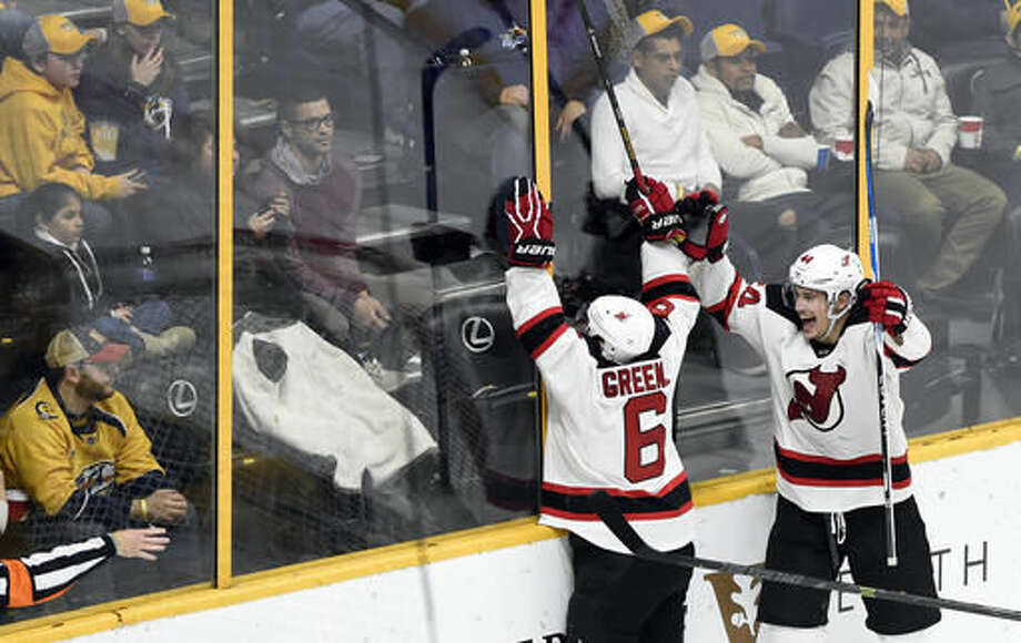 New Jersey Devils defenseman Andy Greene (6) and left wing Miles Wood (44) celebrate after Greene scored a goal against the Nashville Predators during the third period of an NHL hockey game, Saturday, Dec. 3, 2016, in Nashville, Tenn. The Devils won in overtime 5-4. (AP Photo/Mark Zaleski)