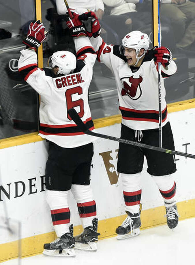 New Jersey Devils defenseman Andy Greene (6) and left wing Miles Wood (44) celebrate after Greene scored a goal against the Nashville Predators during the third period of an NHL hockey game Saturday, Dec. 3, 2016, in Nashville, Tenn. The Devils won in overtime 5-4. (AP Photo/Mark Zaleski)