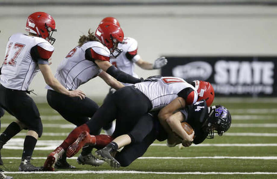 Odessa-Harrington running back Josh Clark, right, is tackled by Neah Bay linebacker Nate Tyler, second from right, in the first half of the Washington Div. 1B high school football championship, Saturday, Dec. 3, 2016, in Tacoma, Wash. (AP Photo/Ted S. Warren)