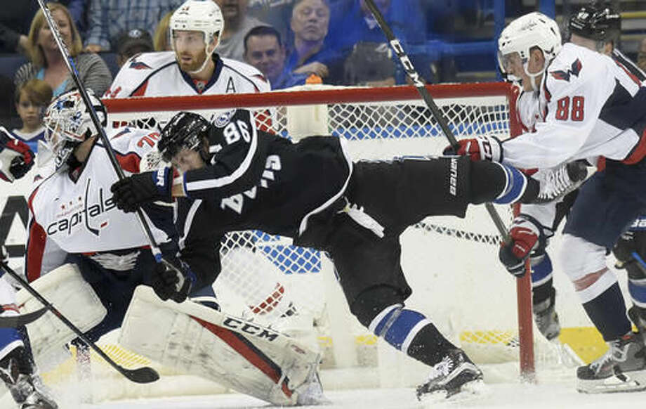 Tampa Bay Lightning right wing Nikita Kucherov (86) tries to get past Washington Capitals defenseman Nate Schmidt (88) and goalie Braden Holtby (70) during the first period of an NHL hockey game Saturday, Dec. 3, 2016, in Tampa, Fla. (AP Photo/Jason Behnken)