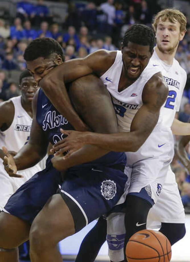 Akron's Isaiah Johnson, left, and Creighton's Cole Huff (13) struggle for a loose ball during the first half of an NCAA college basketball game in Omaha, Neb., Saturday, Dec. 3, 2016. (AP Photo/Nati Harnik)