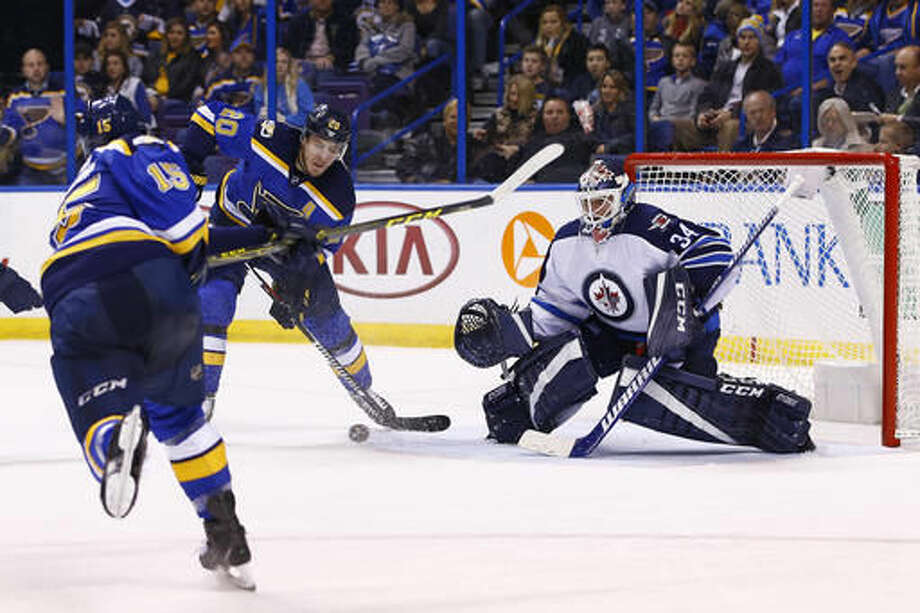 Winnipeg Jets' goalie Michael Hutchinson defends a shot by St. Louis Blues' Robby Fabbri, left, as Alexander Steen, middle, plays the rebound during the second period of an NHL hockey game, Saturday, Dec. 3, 2016, in St. Louis. (AP Photo/Billy Hurst)