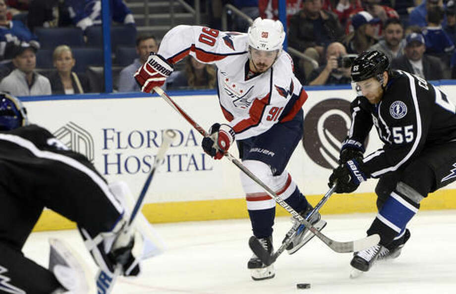 Tampa Bay Lightning defenseman Braydon Coburn (55) knocks the puck away as Washington Capitals left wing Marcus Johansson (90) looks for a shot during the first period of an NHL hockey game Saturday, Dec. 3, 2016, in Tampa, Fla. (AP Photo/Jason Behnken)