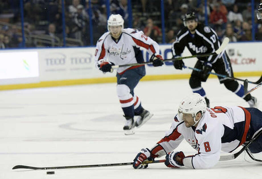 Washington Capitals left wing Alex Ovechkin (8) handles the puck as he is tripped during the first period of an NHL hockey game against the Tampa Bay Lightning, Saturday, Dec. 3, 2016, in Tampa, Fla. (AP Photo/Jason Behnken)