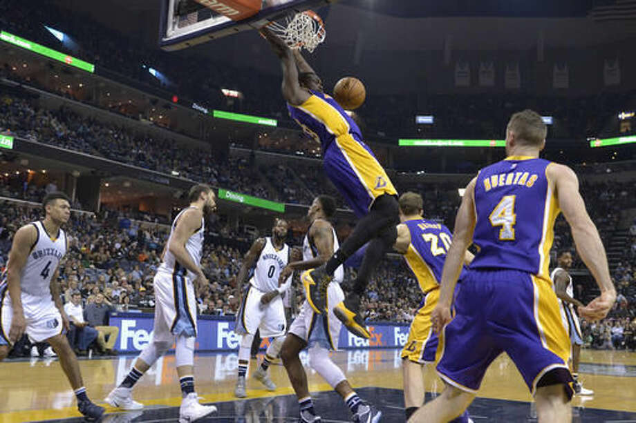 Los Angeles Lakers forward Luol Deng (9) hangs from the rim after dunking the ball in the first half of an NBA basketball game against the Memphis Grizzlies Saturday, Dec. 3, 2016, in Memphis, Tenn. (AP Photo/Brandon Dill)