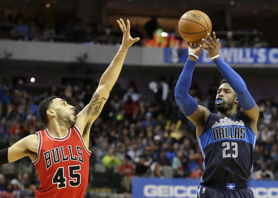 Dallas Mavericks guard Wesley Matthews (23) shoots against Chicago Bulls guard Denzel Valentine (45) during the second half of an NBA basketball game in Dallas, Saturday, Dec. 3, 2016. (AP Photo/LM Otero)