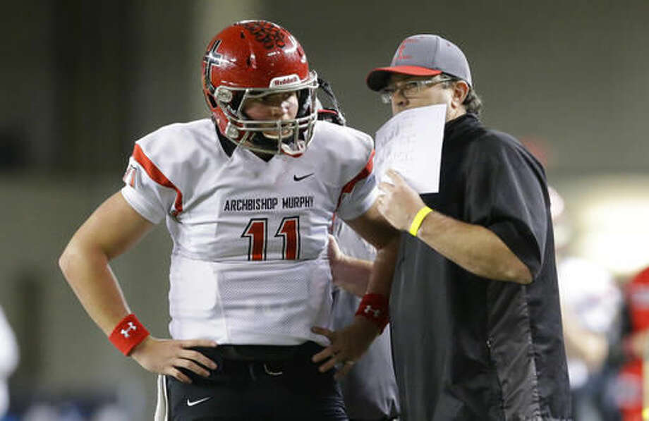 Archbishop Murphy quarterback Connor Johnson, left, confers with head coach Jerry Jensen during the first half of the Washington Div. 2A high school football championship against Liberty, Saturday, Dec. 3, 2016, in Tacoma, Wash. (AP Photo/Ted S. Warren)
