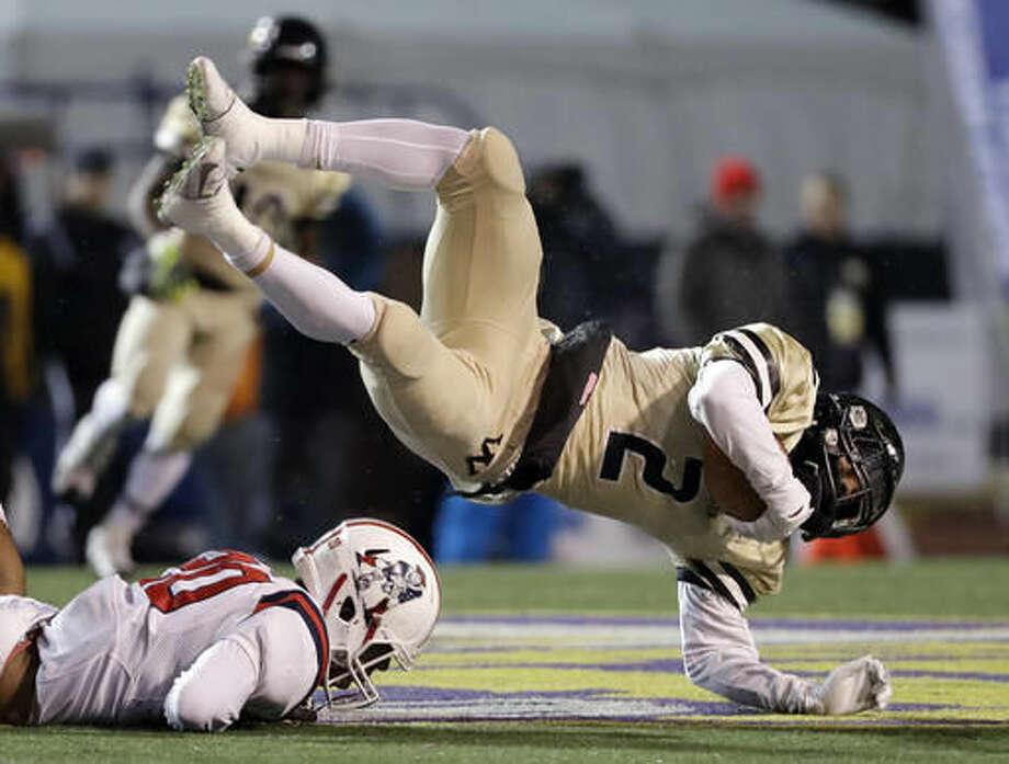 Whitehaven High School wide receiver Markerion Johnson (2) falls over Oakland High School linebacker Brandon Turner (20) during the first half of the Division I Class 6A Tennessee high school football championship game Saturday, Dec. 3, 2016, in Cookeville, Tenn. (AP Photo/Mark Humphrey)