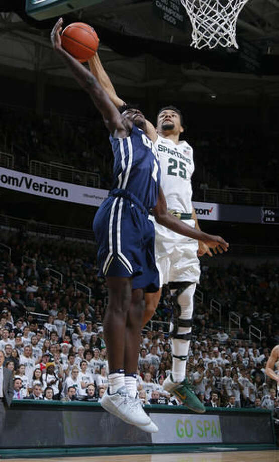 Michigan State's Kenny Goins, right, blocks a fast-break shot attempt by Oral Roberts' Kris Martin during the first half of an NCAA college basketball game, Saturday, Dec. 3, 2016, in East Lansing, Mich. (AP Photo/Al Goldis)