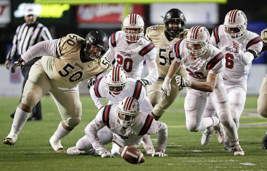 Whitehaven High School and Oakland High School players, including Whitehaven's Tyler Walton (50) and Oakland's JaCoby Stevens, bottom center, chase down the ball after Whitehaven quarterback Lesley Mosby fumbled during the first half of the Division I Class 6A Tennessee high school football championship game Saturday, Dec. 3, 2016, in Cookeville, Tenn. Oakland recovered the ball. (AP Photo/Mark Humphrey)