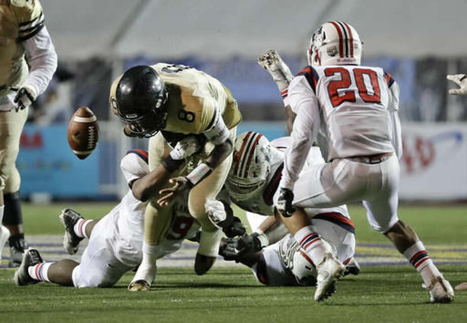 Whitehaven High School quarterback Lesley Mosby (8) fumbles the ball as he is hit during the first half of the Division I Class 6A Tennessee high school football championship game against Oakland High School Saturday, Dec. 3, 2016, in Cookeville, Tenn. Oakland recovered the ball. (AP Photo/Mark Humphrey)