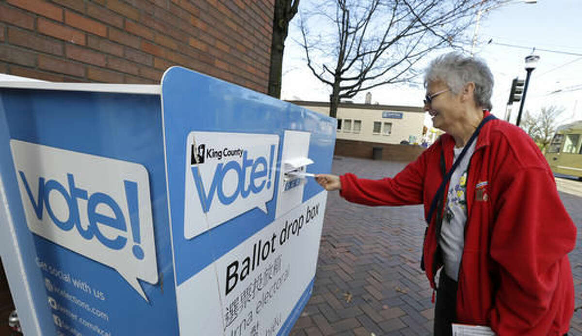 Barb Kearney-Schupp deposits her vote-by-mail ballot in a collection box, Thursday, Nov. 3, 2016, at Seattle Central College in Seattle. More than a million Washingtonians have already cast their ballots in advance of Tuesday's election, as voters decide on federal and state races, as well as ballot initiatives. (AP Photo/Ted S. Warren)