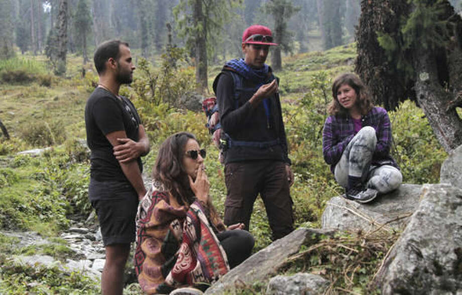 In this Wednesday, Oct. 5, 2016 photo, Israeli tourist Amit, only one name given, seated left, smokes a joint after a hike with friends at Malana village in the northern Indian state of Himachal Pradesh. Malana has become one of the world's top stoner destinations, and a symbolical battleground for India's fight against 'charas,' the black and sticky hashish that has made the village famous. The valley in the Indian Himalayas is teeming with young Israelis, many draped in colorful shawls and wearing their hair into ropey dreadlocks, who come for a therapeutic experience after years of military service. (AP Photo/Rishabh R. Jain)