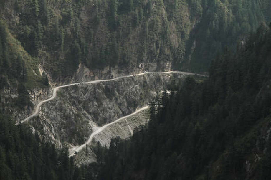 In this Tuesday Oct. 4, 2016 photo, cars move on the narrow shabby road cut along the steep slope near Malana village in the northern Indian state of Himachal Pradesh. Nestled deep in the higher reaches of the Indian Himalayas, Malana has become one of the world's top stoner destinations, and a symbolical battleground for India's fight against 'charas,' the black and sticky hashish that has made the village famous. (AP Photo/Rishabh R. Jain)