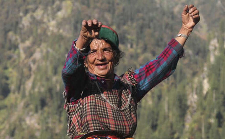 In this Friday, Oct. 7, 2016 photo, Gori Massi sings and dances on the way to work in her cannabis field in Malana village in the northern Indian state of Himachal Pradesh. Every morning, Massi slowly starts the trek to her field, sometimes singing to herself as she walks up a rocky trail. Walking at a pace of a 20-year-old, the wrinkles on her face and hands are the only indication of her age; she is 80. It will take her an hour to get to her plants that are hidden far away from the village near the forest line. She will sit there all day, curing high-potency marijuana buds and rubbing them between her palms to juice out the resin that smears her hands black. (AP Photo/Rishabh R. Jain)
