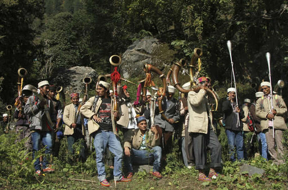In this Thursday, Oct. 6, 2016 photo, local villagers prepare to take a statue of the village god Jamlu on a pilgrimage in Malana village in the northern Indian state of Himachal Pradesh. The journey across the daunting mountain of Rasol is undertaken to bathe the deity in holy water in a temple in the neighboring valley. Its laws, tradition says, were laid down by the village god Jamlu. Nestled deep in the higher reaches of the Indian Himalayas, Malana has become one of the world's top stoner destinations, and a symbolical battleground for India's fight against 'charas,' the black and sticky hashish that has made the village famous. (AP Photo/Rishabh R. Jain)