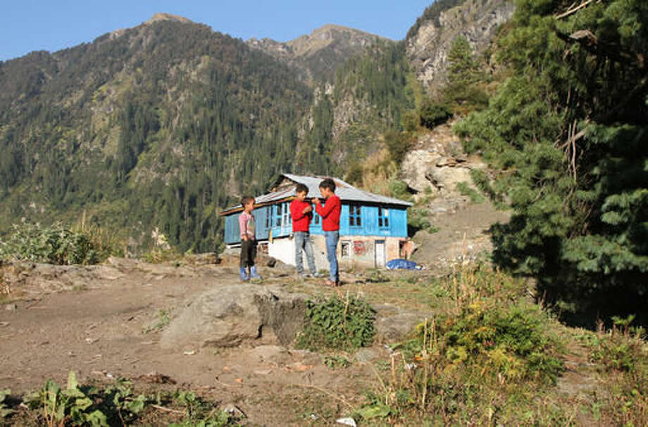 In this Tuesday Oct. 4, 2016 photo, children play in front of a mountain home that stands alone at the upper-end of the Malana village in the northern Indian state of Himachal Pradesh. Nestled deep in the higher reaches of the Indian Himalayas, Malana has become one of the world's top stoner destinations, and a symbolical battleground for India's fight against 'charas,' the black and sticky hashish that has made the village famous. (AP Photo/Rishabh R. Jain)