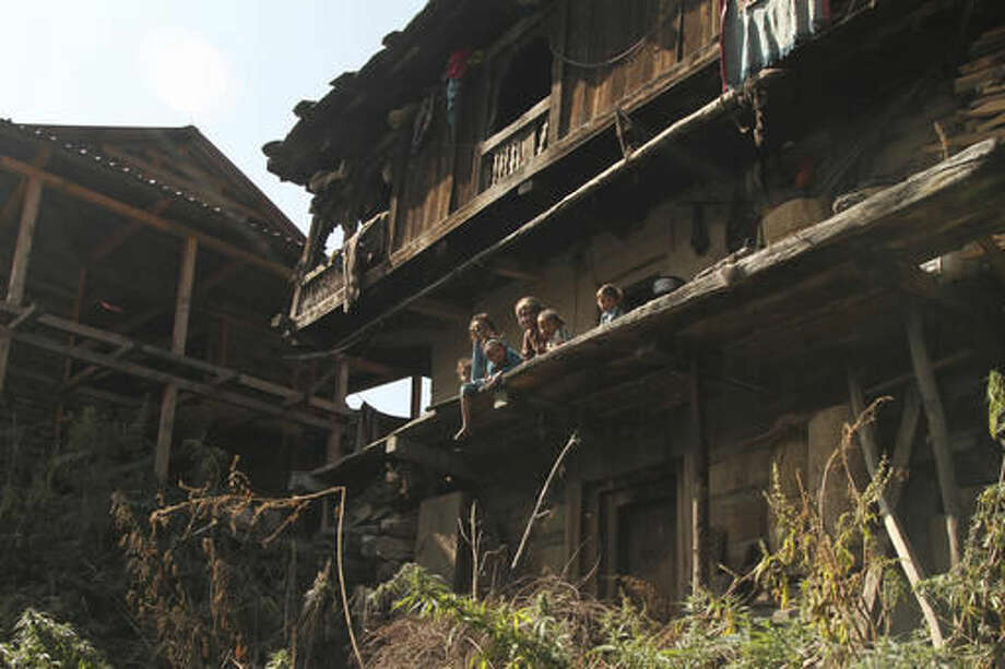 In this Thursday, Oct. 6, 2016 photo, an elderly woman sits with children outside a traditional wooden mountain home in Malana village in the northern Indian state of Himachal Pradesh. In the sleepy mountainous states of North India, marijuana has grown indigenously for hundreds of years. Local lawmakers and officials say the plant is a part of their tradition and empathize with people in steep, remote villages who consider cannabis the only cash crop they can grow in harsh weather and geographic conditions. (AP Photo/Rishabh R. Jain)