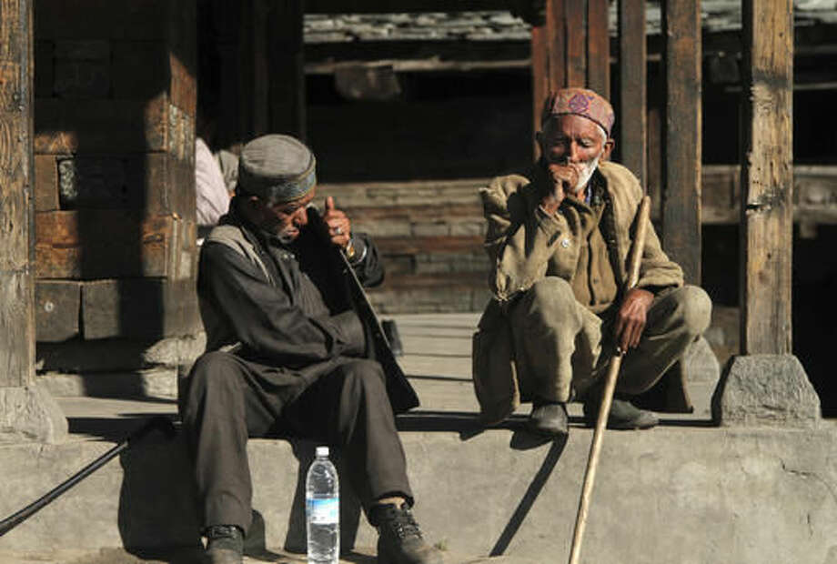 In this Wednesday, Oct. 5, 2016 photo, elderly villagers sunbathe at the village square in Malana in the northern Indian state of Himachal Pradesh. Nestled deep in the higher reaches of the Indian Himalayas, Malana has become one of the world's top stoner destinations, and a symbolical battleground for India's fight against 'charas,' the black and sticky hashish that has made the village famous. (AP Photo/Rishabh R. Jain)