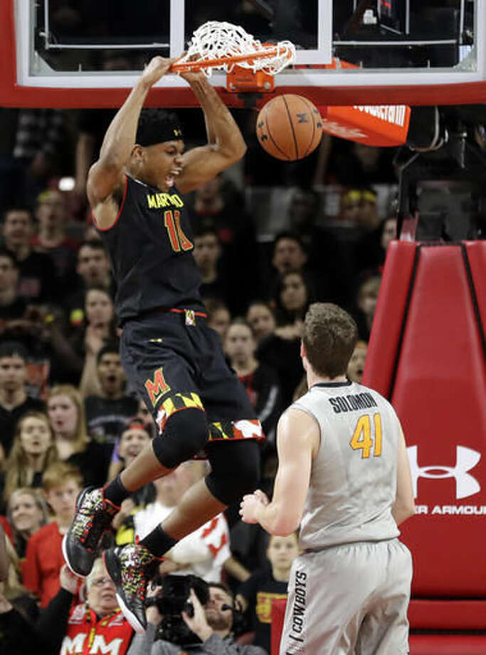 Maryland forward L.G. Gill, top, dunks on Oklahoma State forward Mitchell Solomon in the first half of an NCAA college basketball game, Saturday, Dec. 3, 2016, in College Park, Md. (AP Photo/Patrick Semansky)