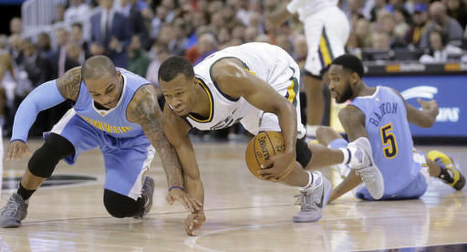 Denver Nuggets guard Jameer Nelson, left, and Utah Jazz guard Rodney Hood, center, battle for a loose ball, as Denver Nuggets guard Will Barton (5) looks on during the first half of an NBA basketball game Saturday, Dec. 3, 2016, in Salt Lake City. (AP Photo/Rick Bowmer)