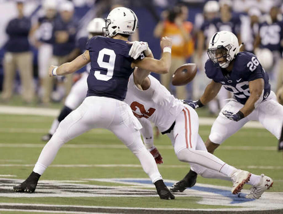Penn State quarterback Trace McSorley (9) fumbles as he is sacked by Wisconsin's T.J. Watt, center, as Penn State's Saquon Barkley, right, watches during the first half of the Big Ten championship NCAA college football game Saturday, Dec. 3, 2016, in Indianapolis. Watt recovered the fumble. (AP Photo/Michael Conroy)