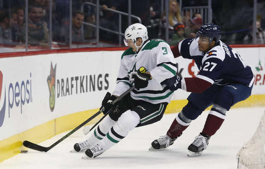 Dallas Stars defenseman John Klingberg, left, of Sweden, fights for control of the puck as Colorado Avalanche left wing Andreas Martinsen, of Norway, defends during the first period of an NHL hockey game Saturday, Dec. 3, 2016, in Denver. (AP Photo/David Zalubowski)