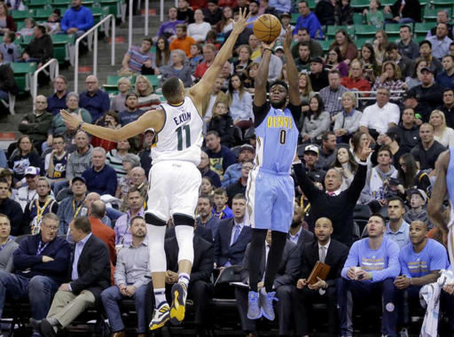 Denver Nuggets guard Emmanuel Mudiay (0) shoots as Utah Jazz guard Dante Exum (11) defends during the first half of an NBA basketball game Saturday, Dec. 3, 2016, in Salt Lake City. (AP Photo/Rick Bowmer)