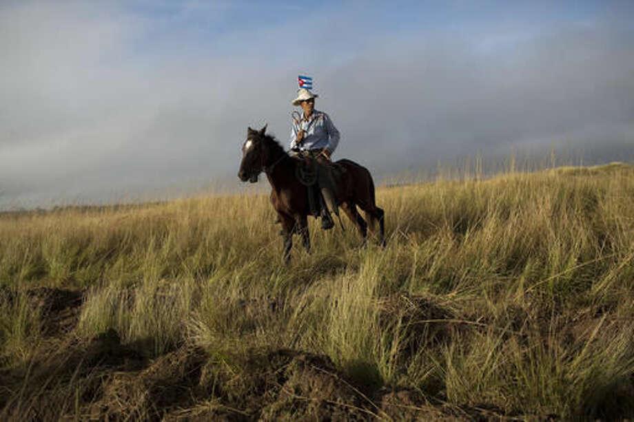 A horseman waits for the funeral procession carrying the ashes of Fidel Castro along the central road in Yarigua, Las Tunas province, Cuba, Friday, Dec. 2, 2016. Castro's ashes are on a four-day journey across Cuba through small towns and cities where his rebel army fought its way to power nearly 60 years ago, to their final resting place in the eastern city of Santiago. (AP Photo/Rodrigo Abd)