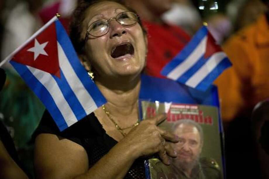 A woman holding portrait of Fidel Castro cries moments after his funeral procession passed by in Bayamo, Cuba, Friday, Dec. 2, 2016. Castro's ashes are on a four-day journey across Cuba through small towns and cities where his rebel army fought its way to power nearly 60 years ago, to their final resting place in the eastern city of Santiago. (AP Photo/Rodrigo Abd)