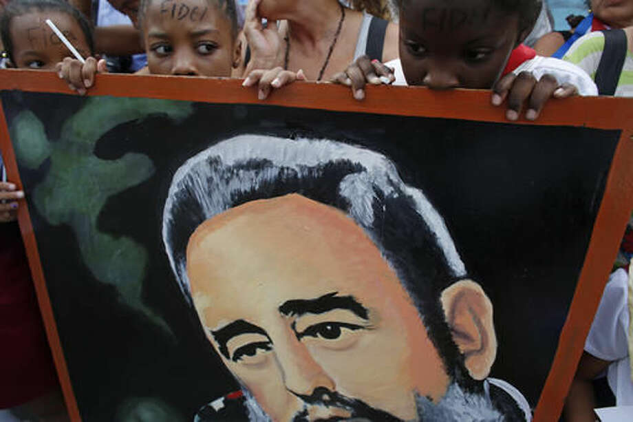 Children stand behind a portrait of the late cuban leader Fidel Castro as they wait for the arrival of the motorcade carrying the ashes of Castro at the Cespedes park in Santiago, Cuba, Saturday, Dec. 3, 2016. After days of national mourning in Cuba and a tour of his ashes through the countryside, his remains have arrived to the city where they will be laid to rest.(AP Photo/Dario Lopez-Mills)