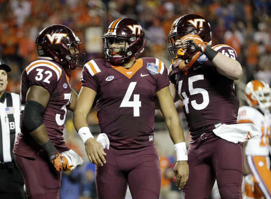 Virginia Tech quarterback Jerod Evans (4), center, is congratulated by fullbacks Steven Peoples (32) and Sam Rogers (45) after Evans scored a touchdown during the first half of the Atlantic Coast Conference championship NCAA college football game against Clemson, Saturday, Dec. 3, 2016, in Orlando, Fla. (AP Photo/Willie J. Allen Jr.)